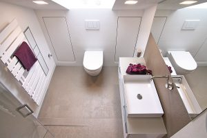 Helle Flächen, eine gekonnte Lichtführung und Stauraum in der Wand zeichnen dieses kleine Bad aus.